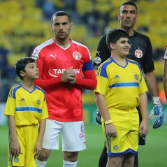 Accompany a player - Home match against Hapoel Beer Sheva (wearing Maccabi Tel Aviv Kit)